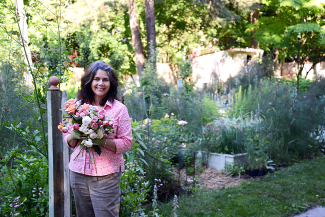 Gloria B. Collins in her Hudson Valley cottage style garden holding freshly cut roses